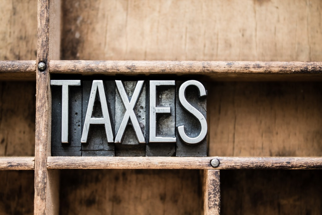 """The word """"TAXES"""" written in vintage metal letterpress type in a wooden drawer with dividers."""